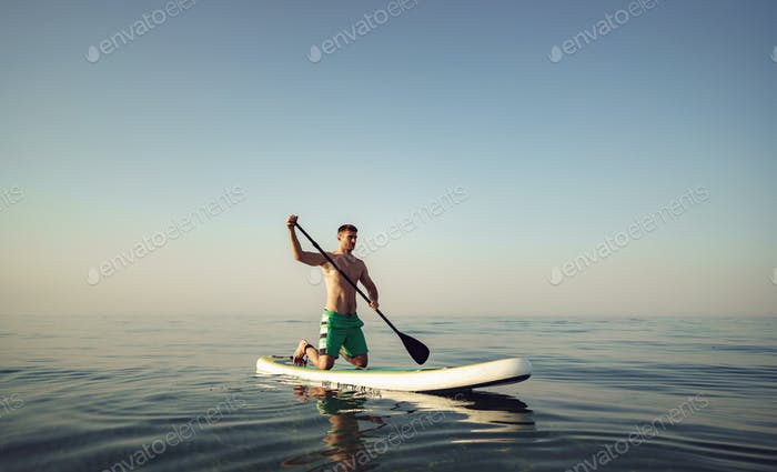 Young fit man on paddle board floating on lake