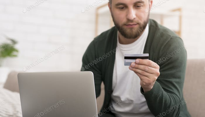 Man shopping online, using credit card to pay