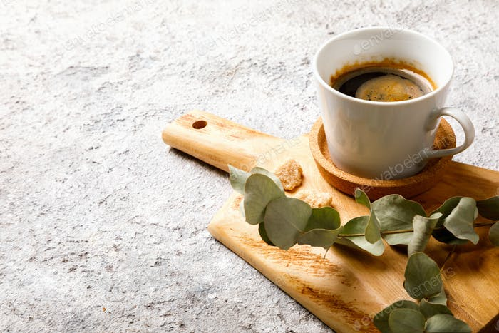 Coffee is hot in a cup on a board with a eucalyptus branch. Breakfast.