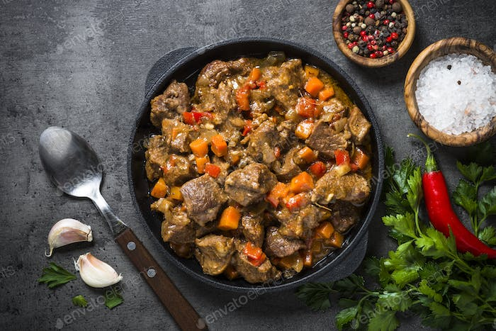 Beef stew with vegetables in iron pan on black