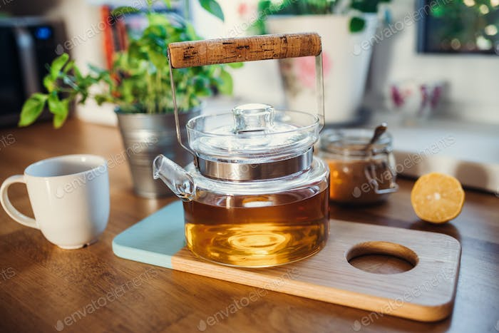Composition of tea in a teapot, sugar, lemon and cup on wooden table.