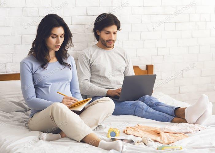 Pregnant woman writing checklist, preparing for maternity hospital