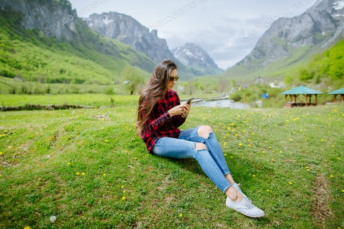 woman with smartphone backpacking in mountains