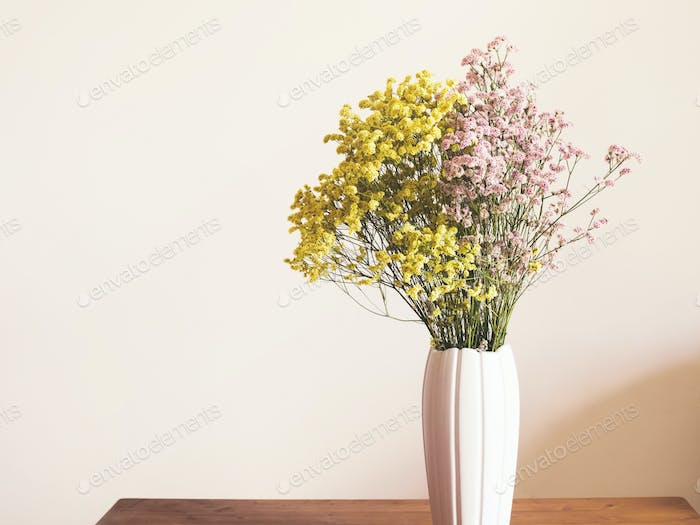 Dried pink and yellow flowers in white vase