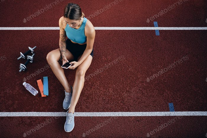 Top view of attractive sporty girl in sportswear with cellphone resting after workout on stadium