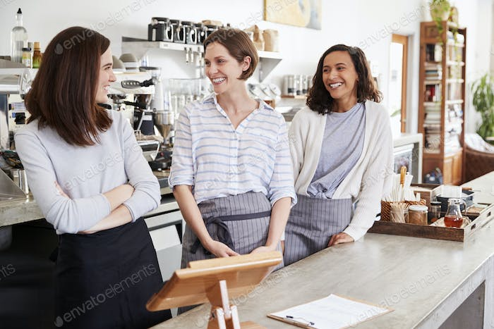 Three female cafe owners looking at each other in cafe