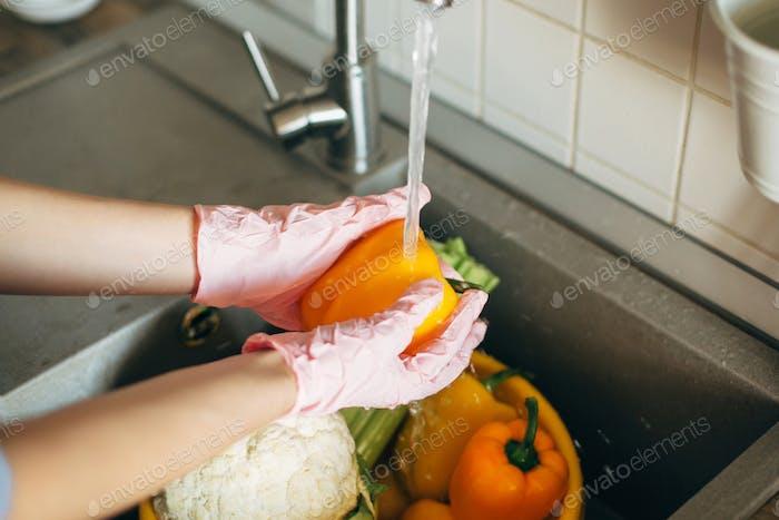 Hands in gloves washing pepper under water stream in sink