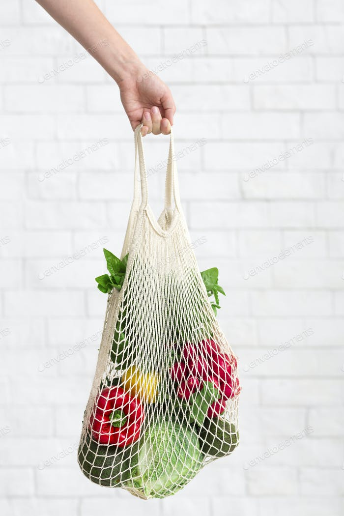 Eco cotton shopping bag with fresh and clean vegetables in woman hand