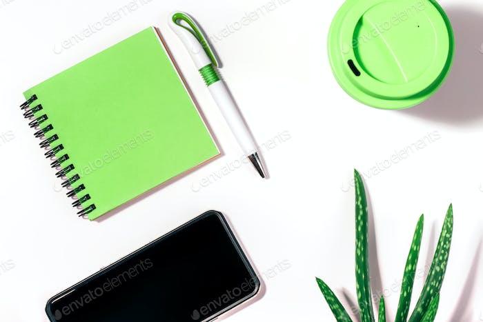 Плоский лежак с обрезанным смартфоном, зеленым блокнотом, ручкой, многоразовой кофейной чашкой и алоэ вера растением