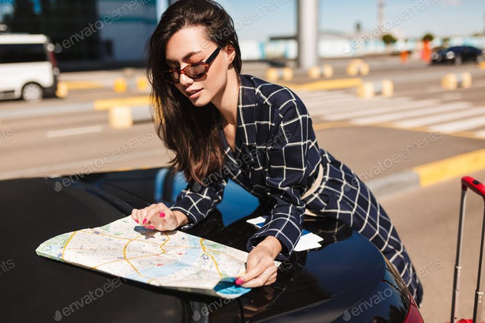 Pretty girl in sunglasses leaning on car dreamily looking road o