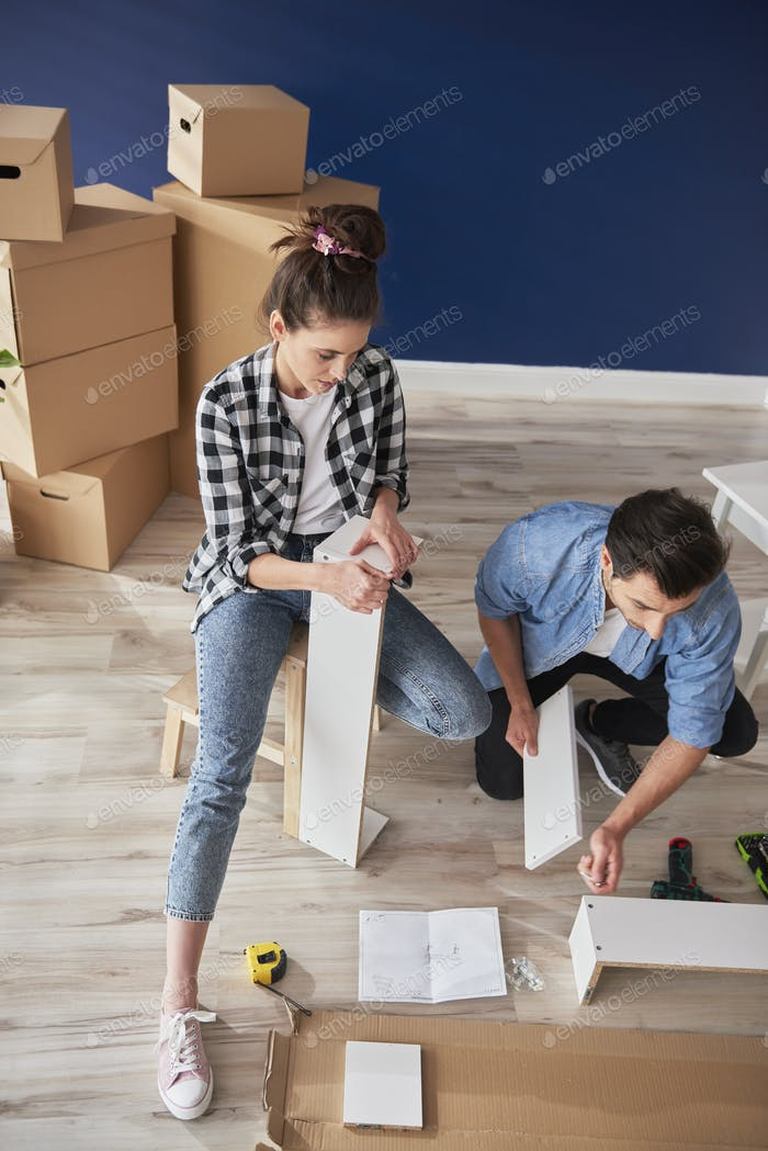 Top view of couple having problem with installing furniture