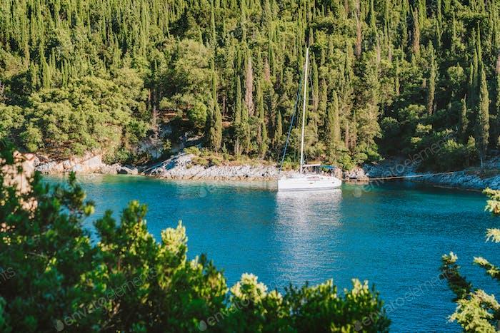 Sail boat yacht moored in the bay of Foki beach surrounded by cypress trees, Fiskardo, Cefalonia