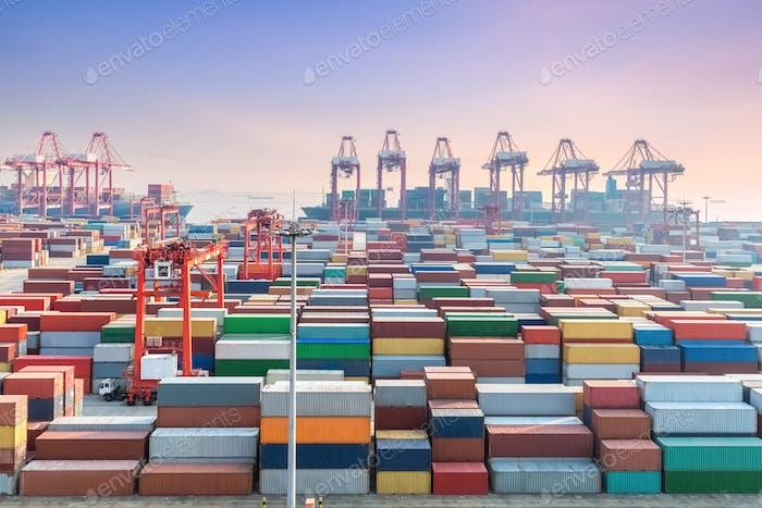 Shanghai Containerterminal in Sonnenuntergang, Containerhof und Ozeandampfer wird Be- und Entladen