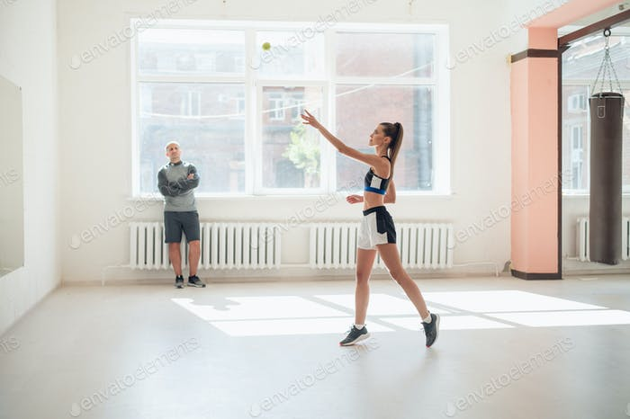 A young girl performs a coach's task for coordination and quick reaction under the guidance of
