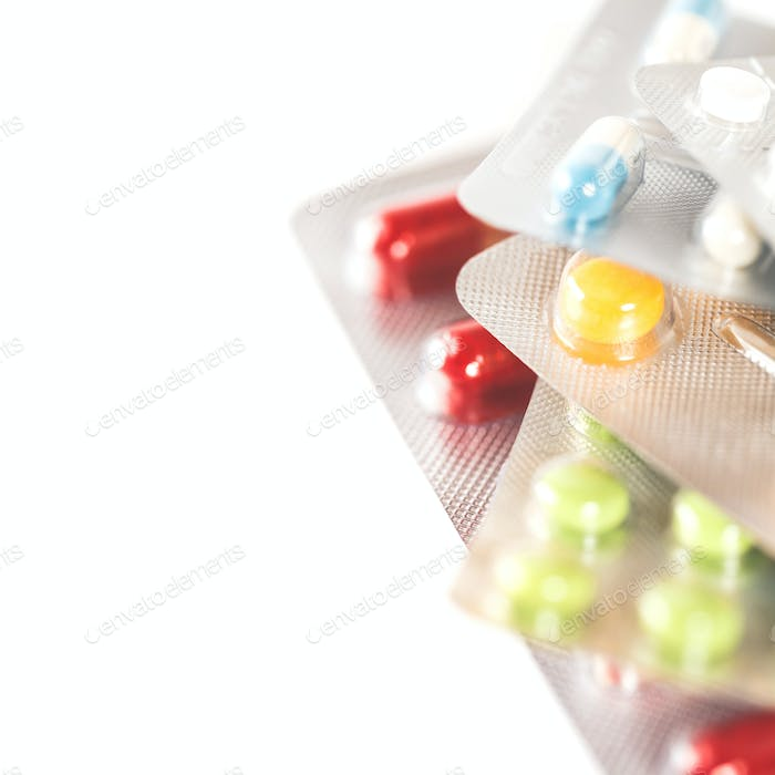 Assorted pharmaceutical medicine pills, tablets and capsules over white background