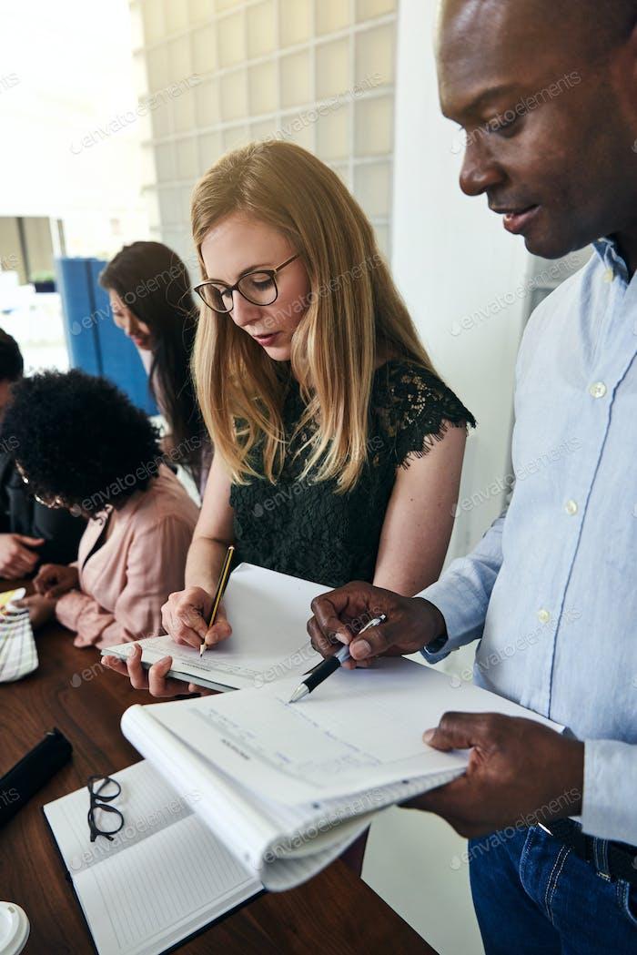 Zwei Geschäftskollegen vergleichen Arbeitsnotizen in einem Büro zusammen
