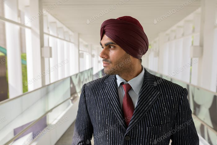 Portrait of Indian businessman with turban thinking outdoors in city
