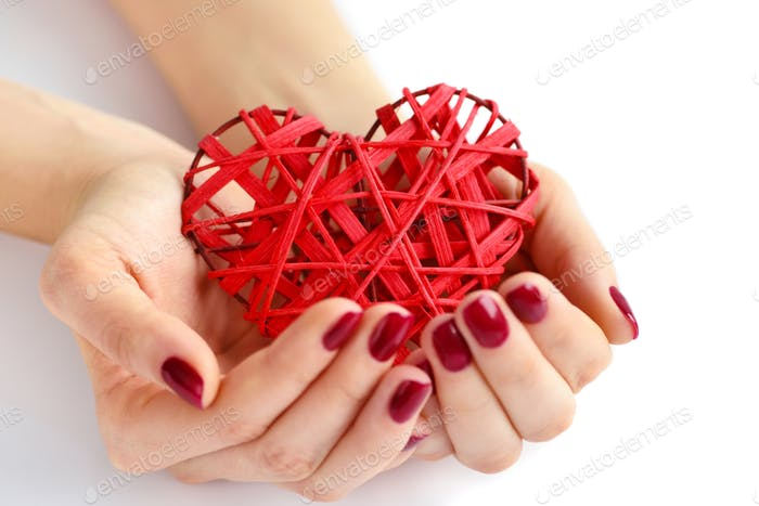 Wicker red heart in woman's hands on white background. Focus on