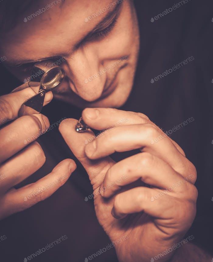 Porträt eines Juweliers während der Bewertung von Juwelen.