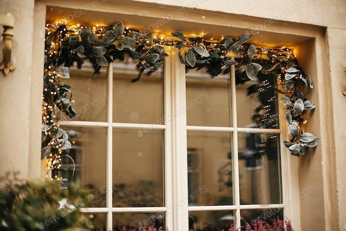 Stilvolle Weihnachts-Mistelzweige mit goldenen festlichen Lichtern am Fenster