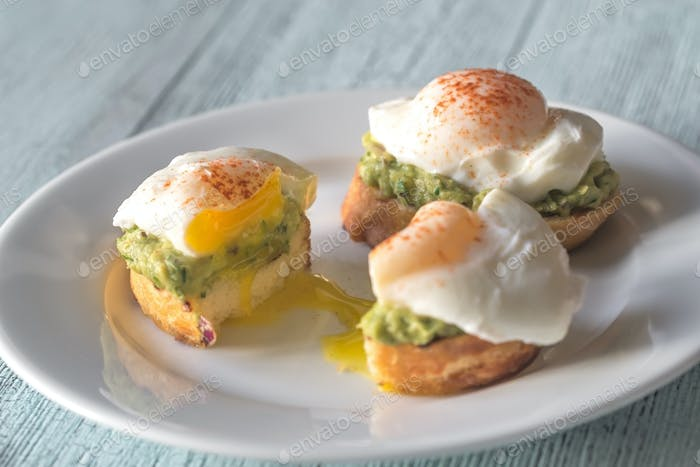 Cut sandwich with guacamole and poached egg