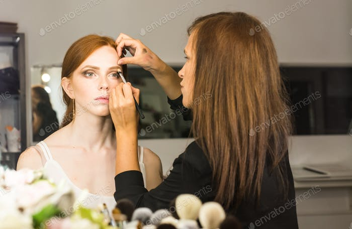 Professional Make-up artist doing glamour model makeup at work