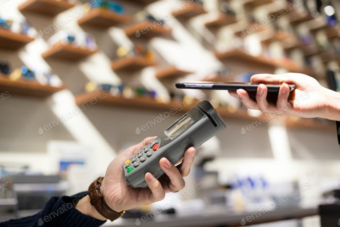 Woman pay by NFC on mobile phone in spectacle shop
