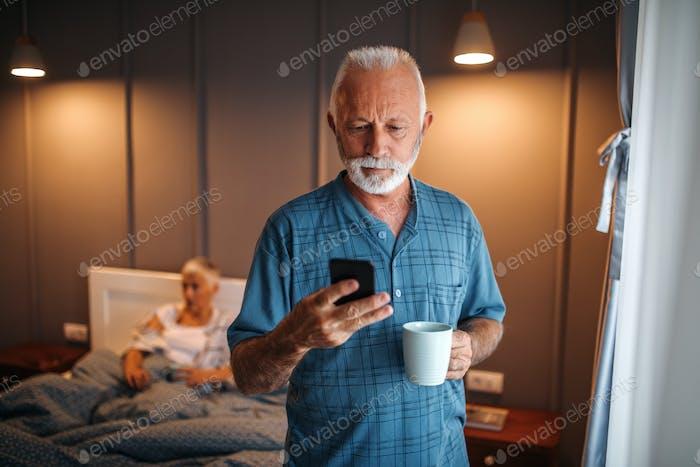 Старший человек, используя смартфон дома
