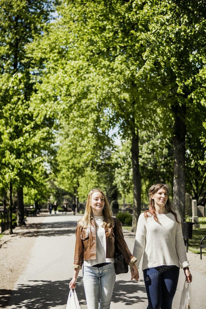 Amigos tomados de la mano mientras camina en la calle en el parque