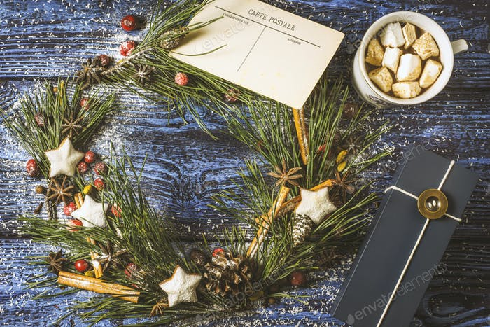 Christmas wreath with postcard and present on the wooden background  top view