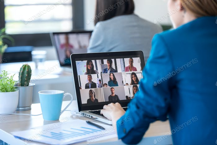 two business women speaking on video call with diverse colleagues on online briefing