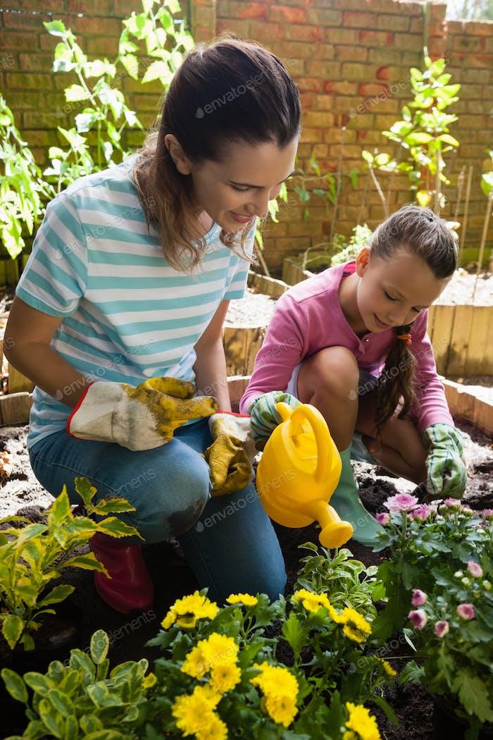 Lächelnde Mutter kniend durch Mädchen Bewässerung Pflanzen