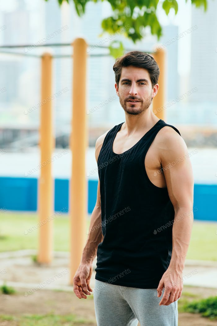 Portrait of Male Personal Trainer Working Out In City Park