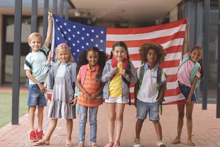 School students standing in outside corridor at school while holding american flag