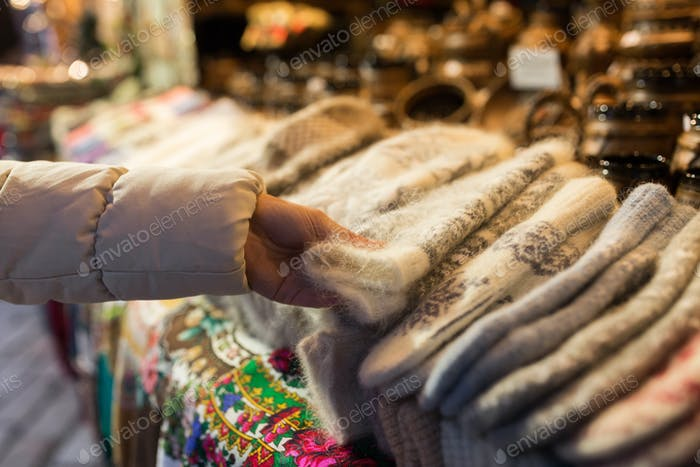 woman buying woolen mittens at christmas market