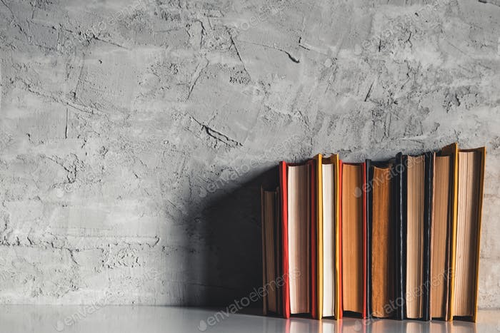 Education and reading concept - group of colorful books on the white table on the gray background