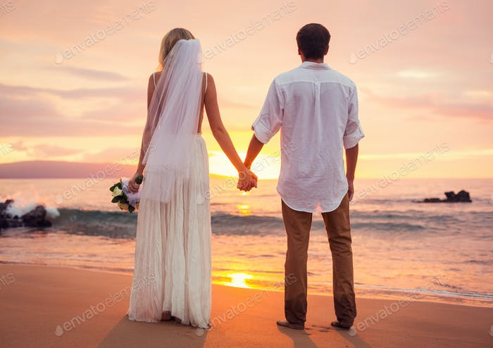 Married couple, bride and groom at sunset on beautiful tropical