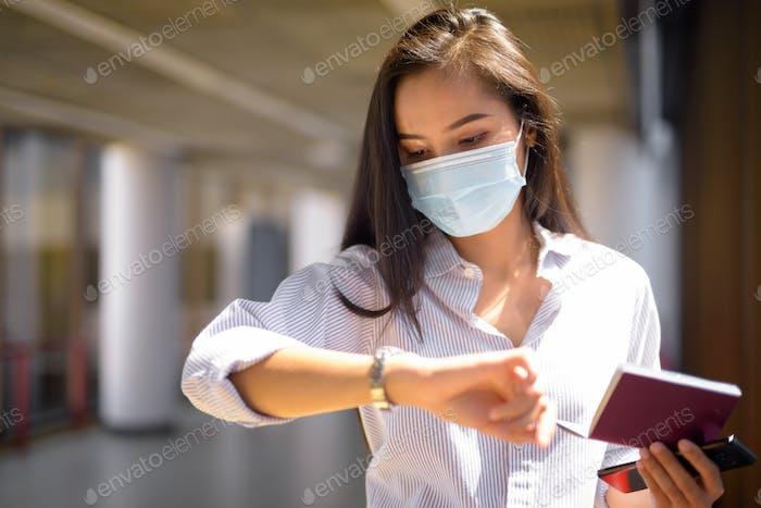 Joven mujer turista asiática con máscara comprobar tiempo mientras que la celebración de pasaporte en el aeropuerto