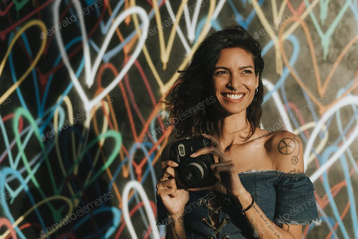 Cheerful woman using an instant camera
