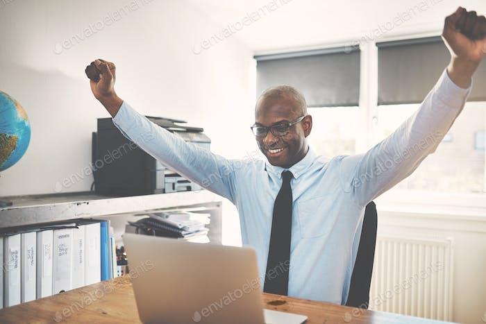 African businessman working on a laptop in an office cheering