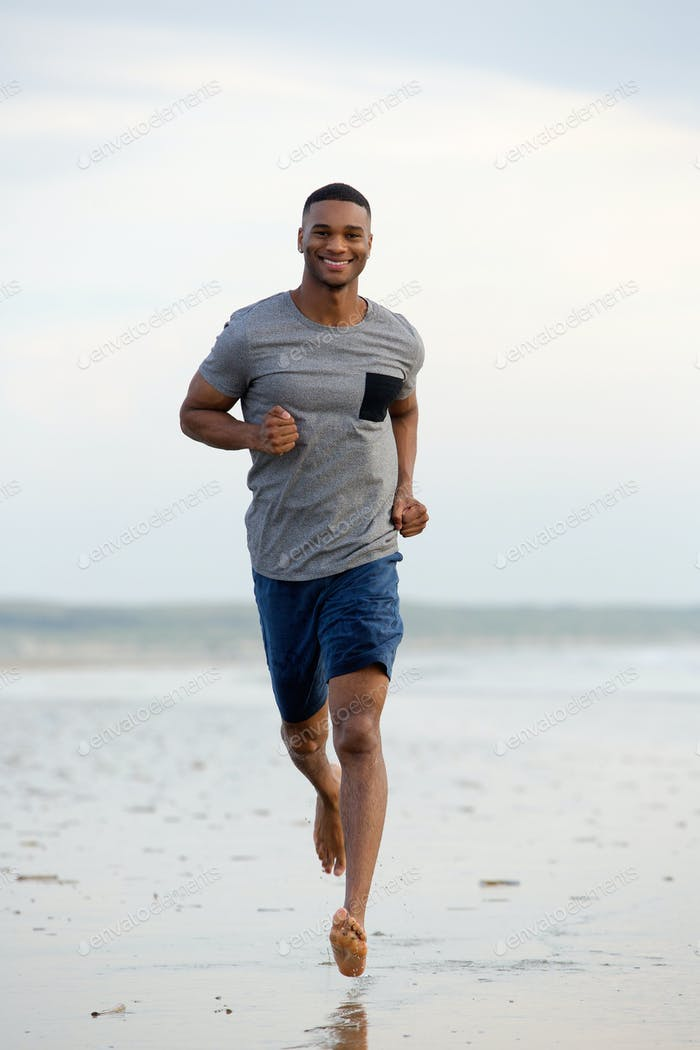 Smiling young man running barefoot