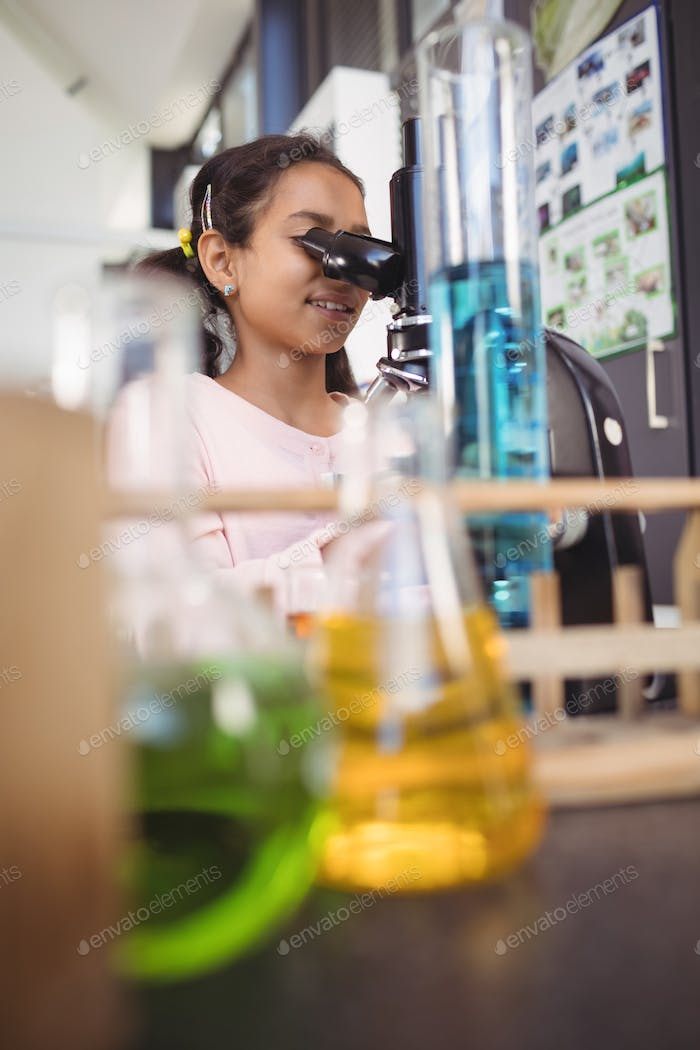 Elementary girl student using microscope at laboratory