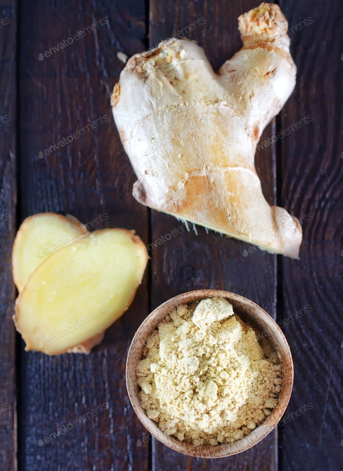 dry ginger in the wooden bowl and on a table
