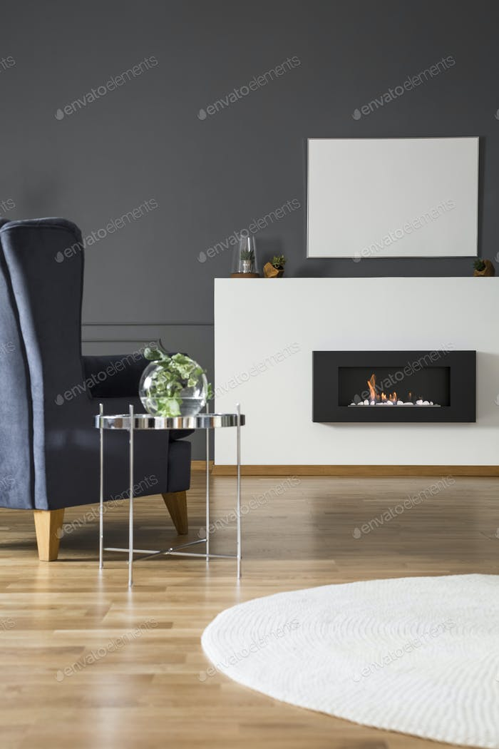 Real photo of a comfy armchair standing in front of a bio firepl