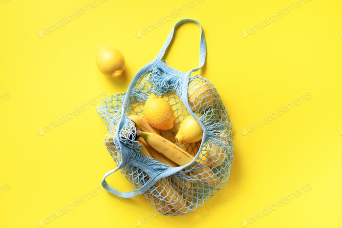 Mesh shopping bag with organic banana, orange, lemons on yellow paper background. Flat lay, top view