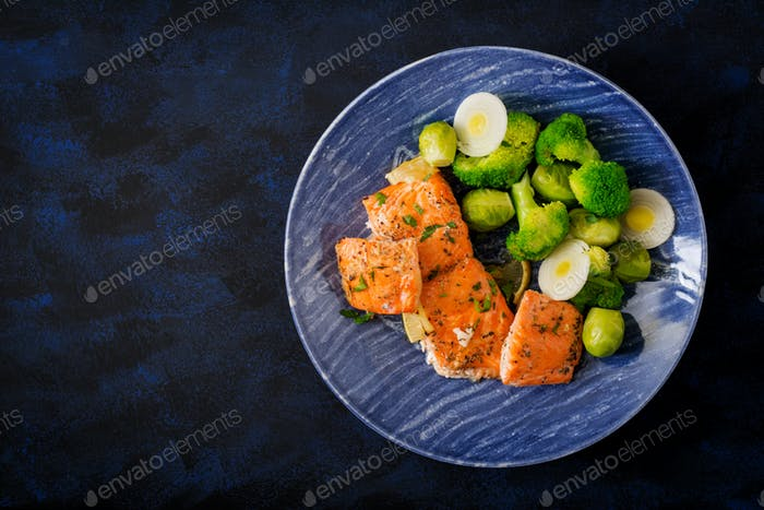 Baked salmon fish garnished with broccoli and Brussels sprouts with leek. Fish menu. Top view.