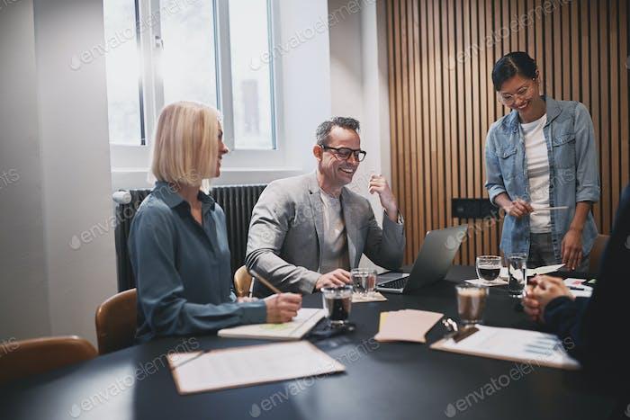 Зрелый бизнесмен смеется во время офисной встречи с коллегами