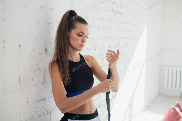 Zu Beginn des Trainings bereitet ein hübsches Kickboxer-Mädchen ihre Hände vor, indem es einen Verband einwickelt