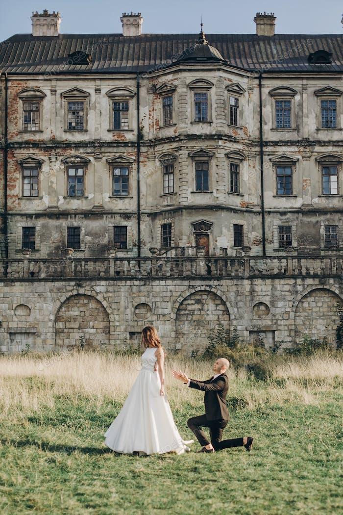 Gorgeous wedding couple walking in sunlight near old castle