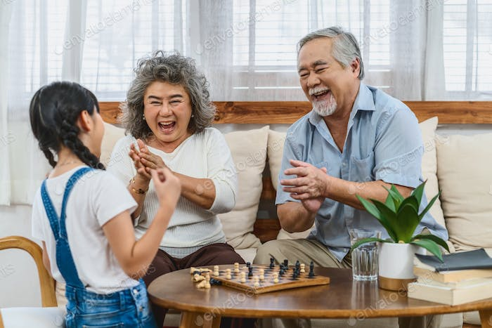 Asian couple Grandparent with grandchild playing the chess with happy feeling together, celebrating